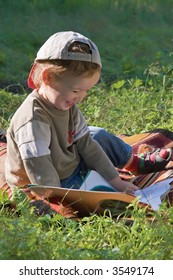 Child reads the book and smiles-summer holiday on a solar glade