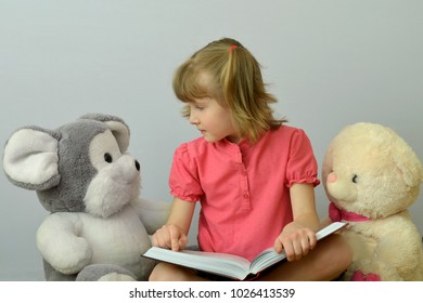 child reads a book of soft toys.