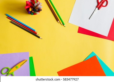 Child ready to draw with pencils and make application of colored paper. Top view.