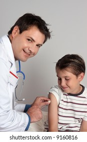 A child receives an immunisation or vaccination shot from a friendly doctor or healthcare worker.