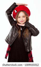 The child in the red beret and jacket is smiling happily and cheerfully. Shows hands a sign - I'm in the house. Child Game.