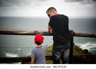 A child in red cap standing behind fence, talking to a man in black t-shirt. Dad talking, teaching his son relationship facing the sea on cloudy rainy day.
