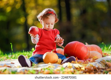 A child in a red dress plays in the open air, in his hands he holds A red apples. The kid sitting next to pumpkins and holding an apple in his hand.
