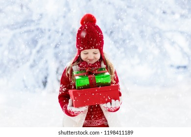 Child in red hat with Christmas presents and gifts in snow. Winter outdoor fun. Kids play in snowy park on Xmas eve. Little girl in knitted sweater, scarf and mittens with Christmas decoration.