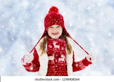 Child in red hat playing in snow on Christmas vacation. Winter outdoor fun. Kids play in snowy park on Xmas eve. Little girl in knitted sweater, scarf and mittens with Christmas decoration.