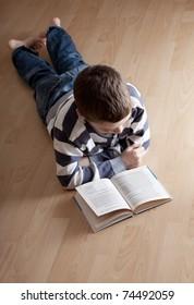Child reeding book lying on the floor