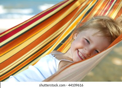 child relaxing in a hammock on the sea beach