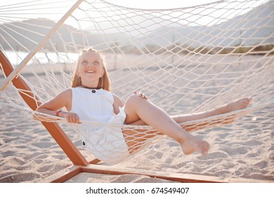 child relaxing on the sea sandy beach on the magic light of sunset. portrait of nice young girl swinging in hummock on tropical coast. Kids summer fashion