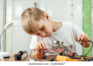 The child remotiruet microcircuit. Workplace with soldering iron, microcircuit, magnifying glass, magnifying glass, measuring instruments. Choice of profession.