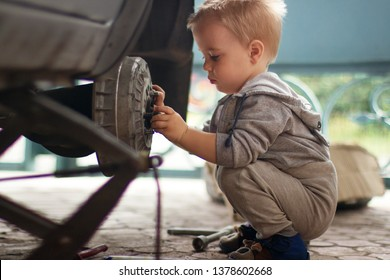 The child repairs the car. The boy changes the wheel. A car on a jack without a wheel.