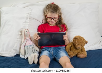 Child is resting at home. Little girl 6, 7 years old sitting in bed with toys, looking at her tablet, smiling.