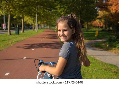 Child rides a bike on a bike path. Cyclist child or teenager girl enjoys good weather and cycling. Environmentally friendly transport concept. Girl is smiling, she is happy.