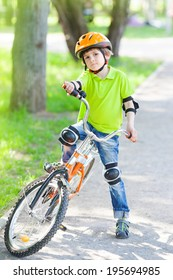 Child rides bike outdoors dressed in a colorful safety helmet