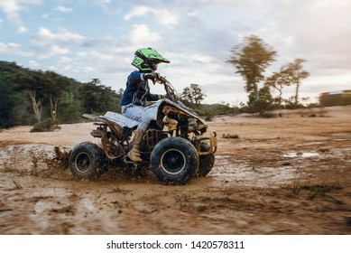 A child rides a quad bike through the mud. ATV rider rides on the dirt