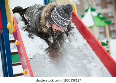 A child rides a slide on the Playground in winter. A boy in a warm coat plays in a snowy winter Park.