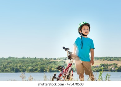Child riding a bicycle. Child with a bicycle on the river bank. Kid in a helmet riding a bike in the forest. Toned image.