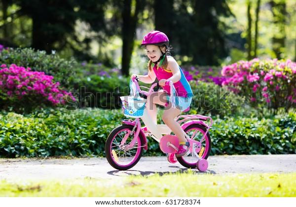 Bicicleta infantil. Niño en bicicleta en un parque soleado. Niña que disfruta de un paseo en bicicleta de camino al colegio en un cálido día de verano. Aprender preescolar para equilibrar la bicicleta con casco seguro. Deporte para niños
