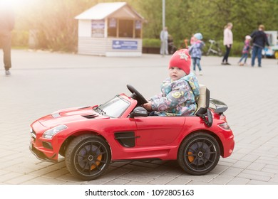 A child is riding an electric car