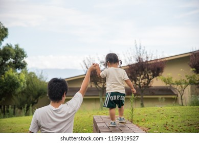 Child riding in high places with help of elder.