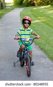 Child Riding His Bike on a Biking Trail in Summer