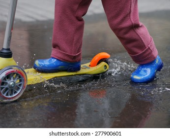 Child riding a plastic tricycle scooter - After the rain - Blue rubber boots