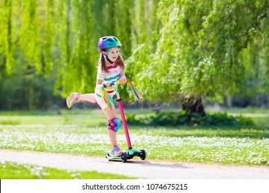 Child riding scooter. Kid on colorful kick board. Active outdoor fun for kids. Summer sports for preschool children. Little girl in spring park. Safety helmet for scooter ride in kindergarten age.