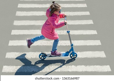 Child riding scooter. Kid on colorful kick board. Active outdoor fun for kids. Sports for preschool children. Little happy girl in spring park. Healthy lifestyle. Eco-friendly transport. Top view