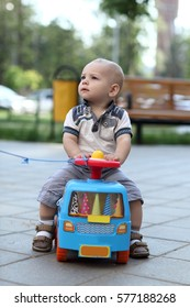 Child riding toy car in the summer park