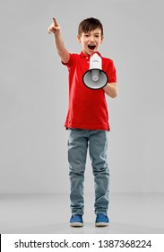 child rights, announcement and people concept - nice little boy in red polo shouting to megaphone over grey background