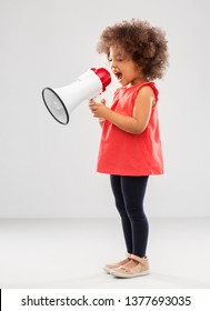 child rights, communication and people concept - happy little african american girl shouting to megaphone over grey background