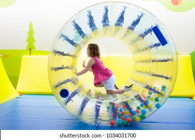 Child in roller wheel jumping on colorful playground trampoline. Kids jump in inflatable bounce castle on kindergarten birthday party. Activity and play center for young child. Little girl playing.