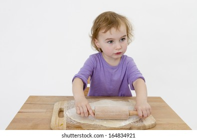 child rolling out dough on small desk. studio shot on grey background