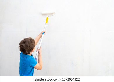 child rolls the roller in the paint on the wall. finishing work in the premises of the artist paints the walls. repair of premises, premises of the house. the child helps to paint the walls.copy space