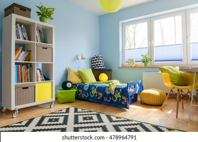 Child room with a bookstand, bed, chair, pouf and big window