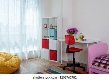 Child room interior with comfortable chair, bed, desk, pouf, big window. Modern baby room with bookstand.