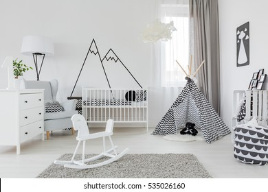 Child room with white furniture, carpet, tent and wall sticker