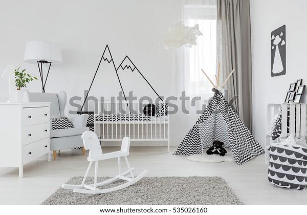 Kinderkamer met wit meubilair, tapijt, tent en muursticker