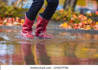 child in rubber boots standing in a puddle in the autumn