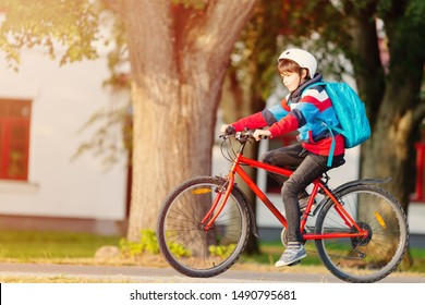 Child with rucksack riding on bikes in the park near school. Pupil with backpack outdoors