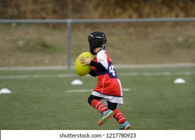 Child rugby player runs with the ball towards the rehearsal line