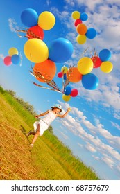 child running with a bunch of colorful balloons in the meadow