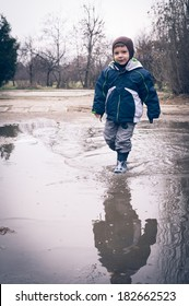 child running in a dirty pool of water