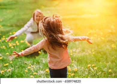 Child running into mother's hands to hug her. Family having fun in the park. Girl is happy to meet her mom. Background image.