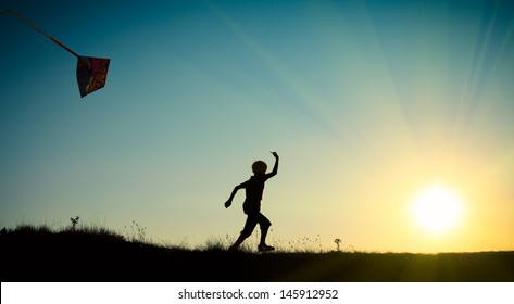 A child running with a kite against the blue sky with the sun