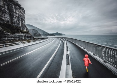 Child running on Sea Cliff Bridge, Grand Pacific Drive, Sydney, Australia. Black and white image with selective coloring.