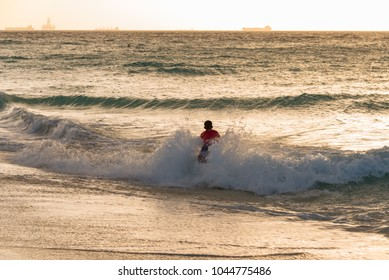 child running on the sea waves at sunset on the Caribbean beach