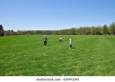 A child running in a park on a large lawn