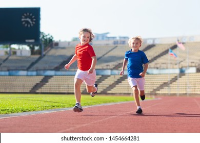 Child running in stadium. Kids run on outdoor track. Healthy sport activity for children. Little girl and boy at athletics competition race. Young athlete training. Runner exercising. Jogging for kid.