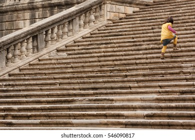 Child running up the stairs of Cathedral of Girona, Catalonia, Spain