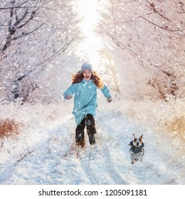 Child runs with a dog in winter. Happy girl with dog outdoors